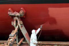 Applicatore che dipinge lo scafo di una barca